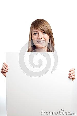 Aantrekkelijke vrouw met leeg teken. Het glimlachen.