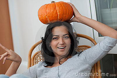 AAttractive girl with holding pumpkins  in here ha