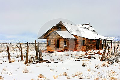 Abandoned homestead on prairie in winter snows