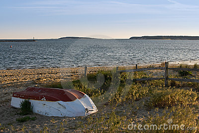 Abandoned small fishing boat on beach at sunset