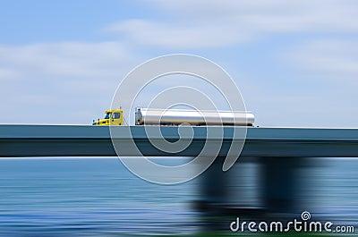 Abasteça o caminhão do petroleiro semi na ponte com borrão de movimento