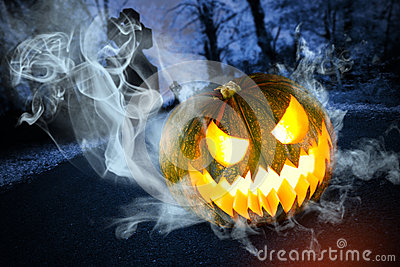Abóbora assustador de Halloween no cemitério na noite