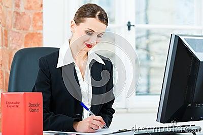 Abogado en la oficina que hace notas en un fichero