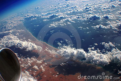 Above the morning Earth, ocean & clouds.