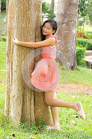 Abrazo de la muchacha el árbol
