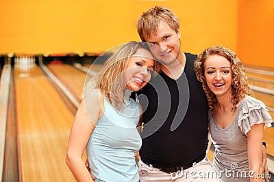 Abrazo del hombre joven y de dos muchachas en club del bowling