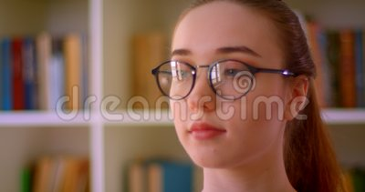 Abschlussportrait junger erfolgreicher Rotkopfweibinnen in Brille mit Blick auf die Bibliothek in Innenräumen stock video footage