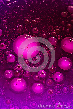 Drops of oil in purple water