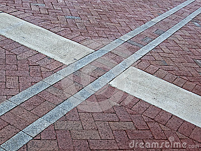 Abstract cross sign on red brick square,