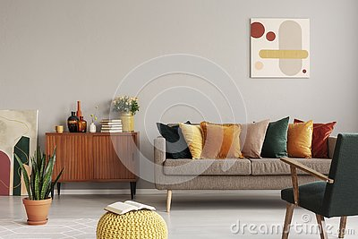 Abstract painting on grey wall of retro living room interior with beige sofa with pillows, vintage dark green armchair and yellow Stock Photo