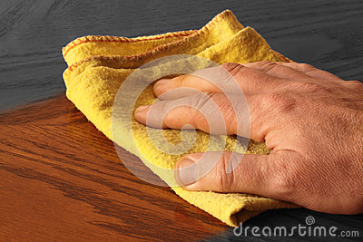 Abstract selective colour image of a man polishing a wooden table