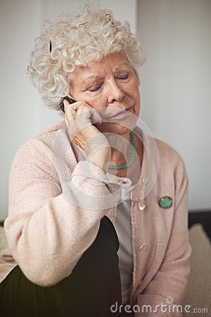 Abuela que comunica usando un teléfono celular
