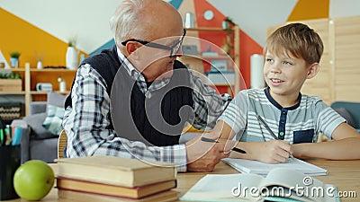 Abuelo ayudando a un hijo menor con tareas domésticas hablando juntos en el escritorio metrajes