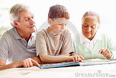 Abuelos que leen un libro de la historia con el nieto