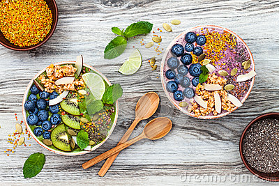 Acai and matcha green tea breakfast superfoods smoothies bowls topped with chia, flax and pumpkin seeds, bee pollen, granola Stock Photo