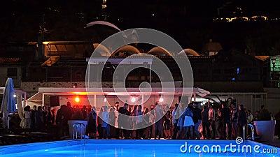 Accende restituire il night-club vicino allo stagno quando la gente balla vago stock footage