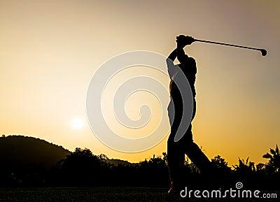 Acción del golfista mientras que puesta del sol