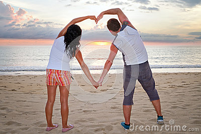 Accouplez effectuer la forme de coeur avec des bras au coucher du soleil