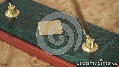 Acessório do negócio grampo Duas penas e pontas tradicionais luxuosas de fonte do vintage em uma tabela de madeira video estoque