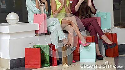 Achat considérant femelle de Shopaholics dans des sacs en papier près des jambes après visite de la boutique à la mode pendant la clips vidéos