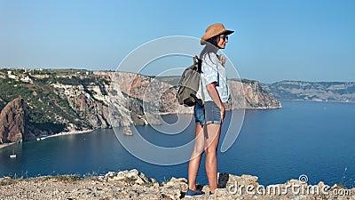Achter de reisvrouw van menings succesvol backpacker het bewonderen verbazend overzees die landschap door berg wordt omringd stock video