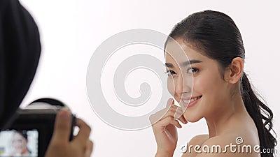 Achter de schermen geschoten van mooi jong Aziatisch vrouwenmodel die op een videocamera worden geregistreerd stock videobeelden
