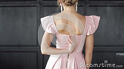Achteraanzicht sexy luxe vrouw die zich in de avondjurk voor elegantie presenteert op oude studio-achtergrond stock videobeelden