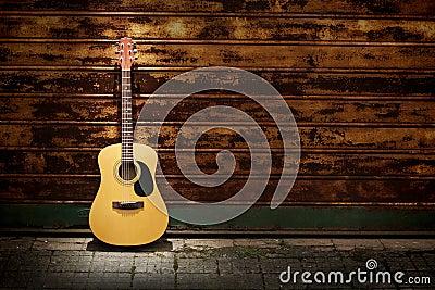 Acoustic guitar against rusty gates