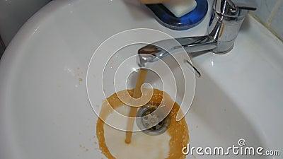 Acqua di rubinetto sporca L'acqua di rubinetto scorre nel lavandino, inizia il marrone arrugginito sporco video d archivio