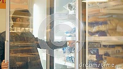 Acquisto bello dell'uomo in un supermercato, prendente alimento congelato dal congelatore archivi video