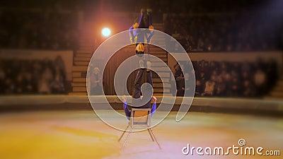 Acrobat voert een moeilijke truc uit in het circus stock videobeelden