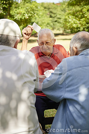 Actieve oudsten, groep oude vriendenspeelkaarten bij park