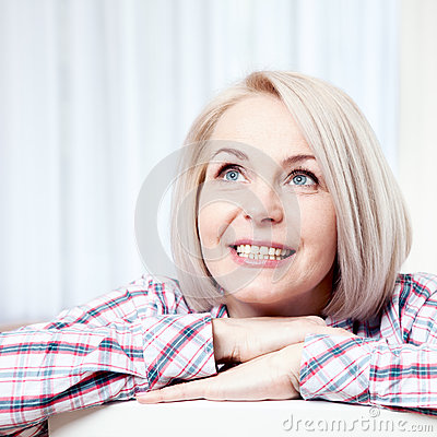 Free Active Beautiful Middle-aged Woman Smiling Friendly And Looking Up At Home In The Living Room. Woman S Face Close Up Stock Photos - 70014203