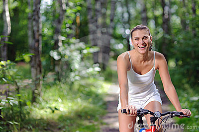 Active brunette woman on red bicycle