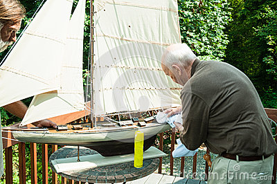 Active Elderly Man and Son with Model Boat
