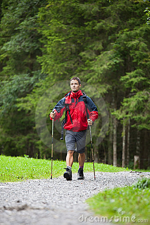Active handsome young man nordic walking