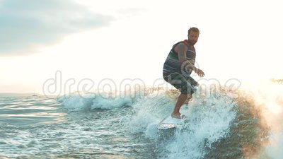 Active man wakesurfing in slow motion. Wakeboarder surfing across river. Active young man wakesurfing in water splashes at sunset. Boy riding wakeboard on stock video