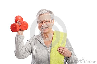 Active old lady with dumbbells smiling