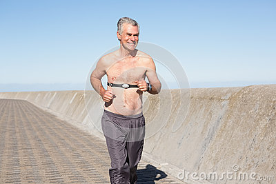 Active shirtless senior man jogging on the pier