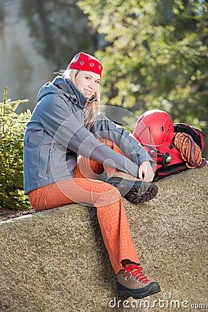Active woman rock climbing sitting backback