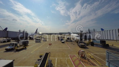 Activity at gates in Chicago airport. Time lapse of people and plane activity at gates of Chicago O'Hare International Airport on sunny day stock video footage