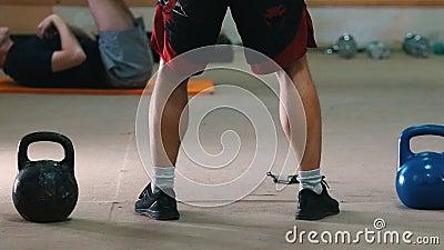 Addestramento sportivo - un uomo atletico in pantaloncini rossi che strizza con un peso nelle mani archivi video