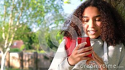 Adolescente afro-americano da menina da raça misturada que inclina-se contra uma árvore usando uma câmera do telefone celular par vídeos de arquivo