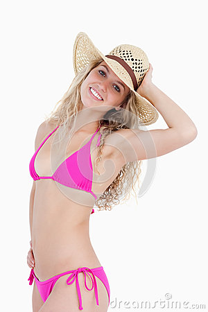 Adolescente biondo sorridente che tiene il suo cappello
