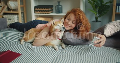 Adolescente che prende selfie con il cane che bacia animale domestico facendo uso della macchina fotografica dello smartphone a c video d archivio
