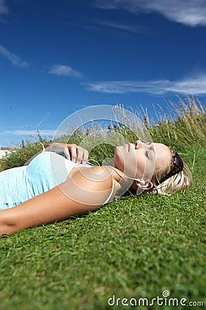 Adolescente che si trova sull erba con il giocatore mp3