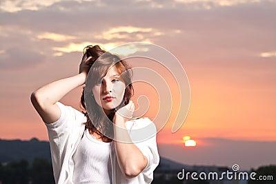 Adolescente joven atractivo en la puesta del sol
