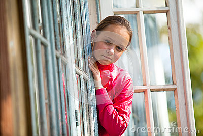 A Adolescente-menina olha para fora a casa rural do indicador