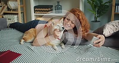 Adolescente que toma o selfie com o cão que beija o animal de estimação usando a câmera do smartphone em casa