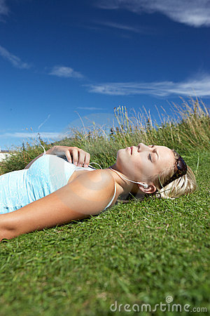 Adolescente se trouvant sur l herbe avec le joueur mp3